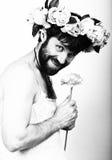 Hombre barbudo en el vestido de la boda de una mujer en su cuerpo desnudo, tenencia una flor En su cabeza una guirnalda de flores Imágenes de archivo libres de regalías