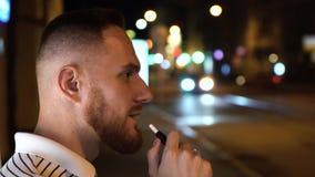 Hombre barbudo en iqos electrónicos del cigarrillo del humo rayado de la camiseta en la noche en la calle con los coches en fondo almacen de metraje de vídeo