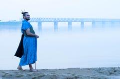 Hombre barbudo en kimono azul con el libro en la orilla del río foto de archivo