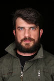 Hombre barbudo en la chaqueta de color caqui que mira en la cámara cierre Encima de negro Fotografía de archivo