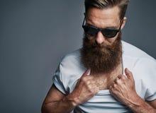 Hombre barbudo en las gafas de sol que muestran el pelo del pecho fotografía de archivo libre de regalías