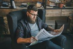 Hombre barbudo en lentes que lee el periódico mientras que se sienta en butaca en casa Fotos de archivo libres de regalías