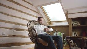 Hombre barbudo en los vidrios que mandan un SMS en mensajero en smartphone en el ático almacen de video