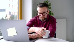 Hombre barbudo en los vidrios que sientan en casa la oficina y que trabajan en un ordenador portátil metrajes