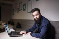 Hombre barbudo en traje y con el ordenador portátil que se sienta en café y que hojea Foto de archivo