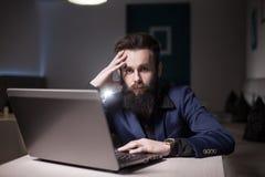 Hombre barbudo en traje y con el ordenador portátil que se sienta en café y que hojea Imagen de archivo