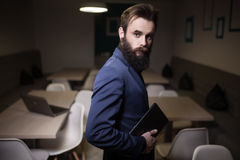 Hombre barbudo en traje y con la tableta en café; Imagen de archivo libre de regalías