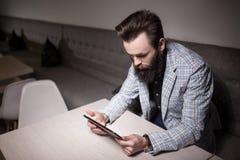 Hombre barbudo en traje y con la tableta que se sienta en café y que hojea Foto de archivo libre de regalías