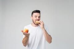 Hombre barbudo en una camisa blanca en un fondo ligero que sostiene una hamburguesa y una manzana Imagen de archivo libre de regalías