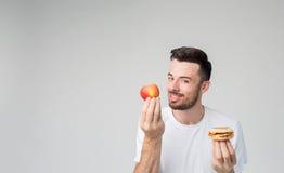 Hombre barbudo en una camisa blanca en un fondo ligero que sostiene una hamburguesa y una manzana Imagen de archivo