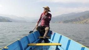 Hombre barbudo en una camisa, un sombrero y gafas de sol rojos en un barco de madera azul que rema los remos en el lago contra el almacen de metraje de vídeo