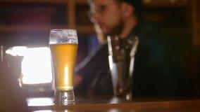 Hombre barbudo en vidrios que bebe la cerveza en la barra almacen de video