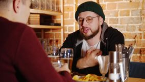 Hombre barbudo en vidrios que habla con su amigo en la barra almacen de metraje de vídeo