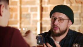 Hombre barbudo en vidrios que habla con su amigo en la barra Cerveza Cierre para arriba almacen de video