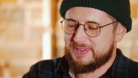 Hombre barbudo en vidrios que habla con su amigo en la barra Cierre para arriba almacen de video