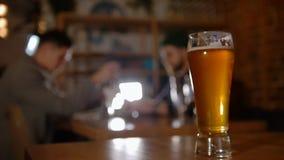 Hombre barbudo en vidrios que habla con su amigo en la barra restaurante Foco sobre el vidrio de cerveza almacen de video