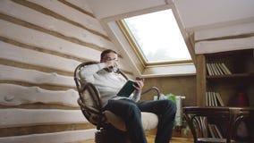 Hombre barbudo en vidrios que lee un libro y que bebe el vino en el ático almacen de video