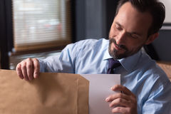Hombre barbudo encantado que mira los documentos imagen de archivo libre de regalías