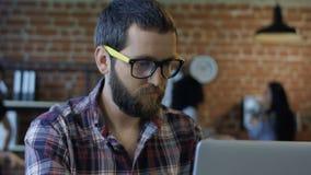 Hombre barbudo enfocado que usa el ordenador almacen de video