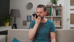 Hombre barbudo enojado, emocional que grita en el smartphone Individuo subrayado y deprimido que llama a la novia y al comienzo metrajes