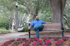Hombre barbudo feliz en botón azul abajo en jardín Fotografía de archivo
