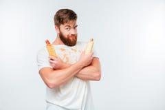 Hombre barbudo feliz en la camisa asquerosa que sostiene dos perritos calientes Imágenes de archivo libres de regalías