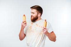 Hombre barbudo feliz en la camisa asquerosa que sostiene dos perritos calientes Imagen de archivo