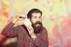 Hombre barbudo feliz que pone el billete de banco en la hucha de cer?mica rosada imágenes de archivo libres de regalías