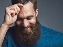 Hombre barbudo feliz que se peina el pelo Imagen de archivo