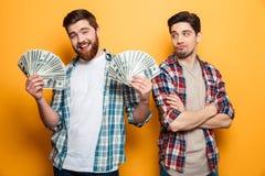 Hombre barbudo feliz que sostiene el dinero y que mira la cámara imagen de archivo libre de regalías