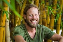 Hombre barbudo feliz, relajado en el jardín de bambú fotos de archivo libres de regalías
