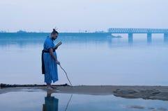 Hombre barbudo gordo en la situación azul del kimono en la orilla del río y la escritura en la arena con el palillo de madera imagen de archivo libre de regalías