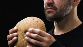 Hombre barbudo hambriento que sostiene el pan, concepto de la pobreza, inseguridad social, primer almacen de metraje de vídeo