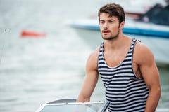 Hombre barbudo hermoso del marinero que conduce su barco de motor Imagen de archivo libre de regalías