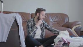 Hombre barbudo hermoso del retrato que se sienta en el piso y las maletas que embalan Concepto de preparaci?n para el viaje almacen de metraje de vídeo