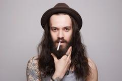hombre barbudo hermoso en el sombrero que fuma un cigarrillo Imagen de archivo libre de regalías