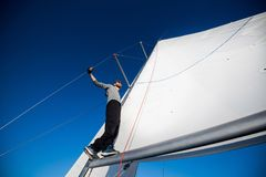 Hombre barbudo hermoso en gafas de sol en una situación de la regata en un auge de la vela foto de archivo libre de regalías
