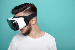 Hombre barbudo hermoso joven que mira abajo con las gafas de la realidad virtual en estudio en fondo colorido Smartphone usando Fotografía de archivo