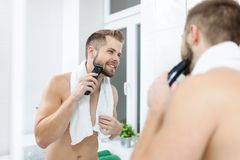 Hombre barbudo hermoso que arregla su barba con un condensador de ajuste fotos de archivo libres de regalías