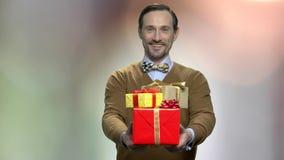 Hombre barbudo hermoso que da las cajas de regalo almacen de metraje de vídeo