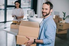 hombre barbudo hermoso que sostiene las cajas de cartón y que sonríe en la cámara mientras que vuelve a poner con el colega femen fotos de archivo
