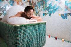 Hombre barbudo hermoso que tiene masaje profesional de la espuma Imagen de archivo