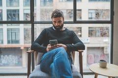 Hombre barbudo hermoso que usa el teléfono móvil y bebiendo el café en casa Concepto casual del tiempo de la relajación y de rest fotos de archivo libres de regalías
