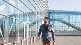 Hombre barbudo hermoso seguro de sí mismo en el traje de moda que tira de la maleta al terminal de aeropuerto Viaje de negocios almacen de metraje de vídeo