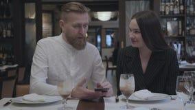 Hombre barbudo hermoso y mujer morena bonita que se sientan en el restaurante en la tabla El hombre muestra a su novia almacen de video