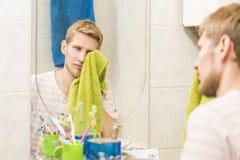 Hombre barbudo joven con la toalla que mira en el espejo en el cuarto de baño, mañana soñolienta imagen de archivo