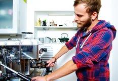 Hombre barbudo joven con su máquina de café express fotos de archivo libres de regalías