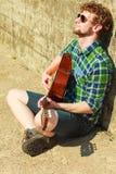 Hombre barbudo joven del inconformista con la guitarra al aire libre Fotos de archivo libres de regalías