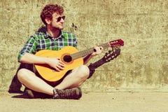Hombre barbudo joven del inconformista con la guitarra al aire libre Foto de archivo libre de regalías