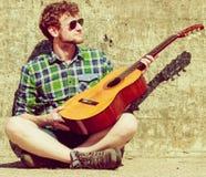 Hombre barbudo joven del inconformista con la guitarra al aire libre Imagen de archivo